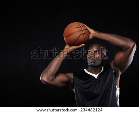 Young african american male basketball player shooting at the hoop against black background - stock photo