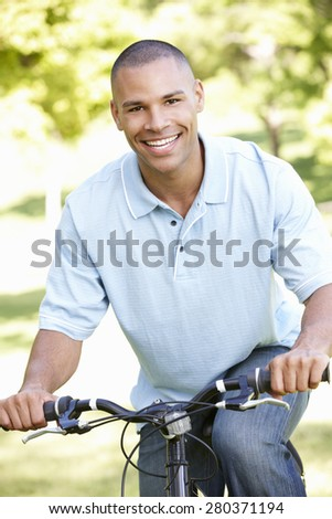 Young African American Man Cycling In Park - stock photo