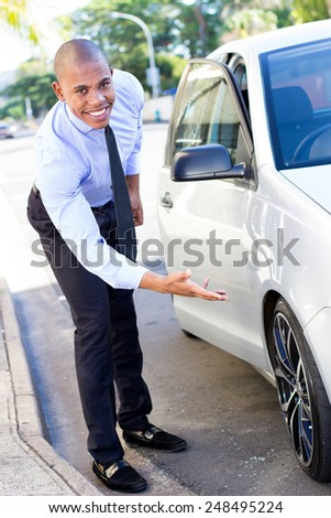 Young African American Man excited about his car, inspecting his wheels - stock photo