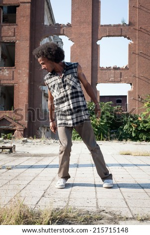Young African American man hip hop dancing in an urban square, lit by a bright sun over high-rise buildings