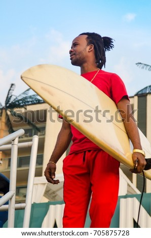 Young African American man holding a surfboard outdoors