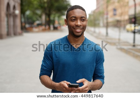 Young African American man in city texting cell phone walking