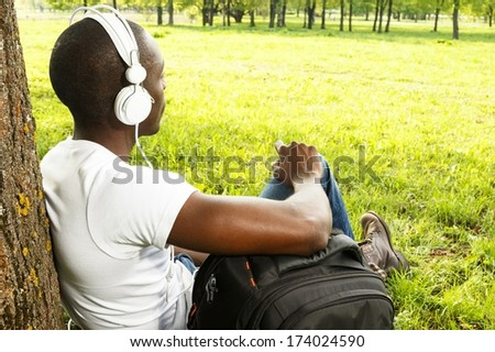 Young african american man in white shirt listens music in a park - stock photo