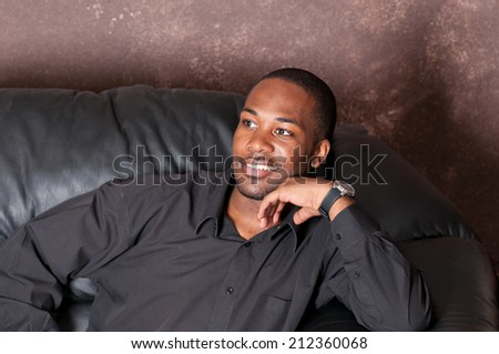 Young African-American man on a black couch - stock photo