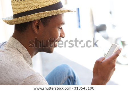 Young african american man reading text message on cell phone - stock photo