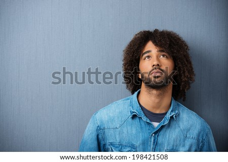 Young African American man standing musing against a grey studio background with copyspace with a serious pensive expression - stock photo