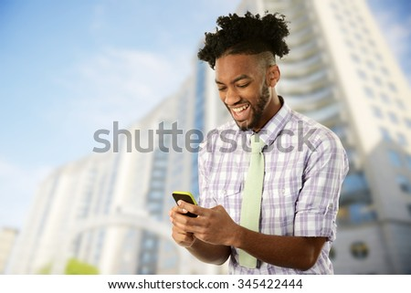 Young African American Man with his cell phone with buildings on the background