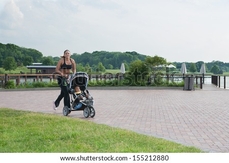 Young African American Mom Running Outdoor with Little Boy in Stroller Under Morning Sun Light - stock photo