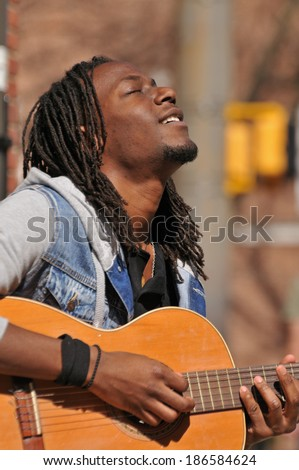 young African American musician playing guitar outside - stock photo