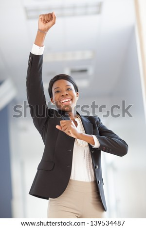 Young African-american professional woman in a hallway, cheering, arms raised, smiling, wearing blazer, pearls