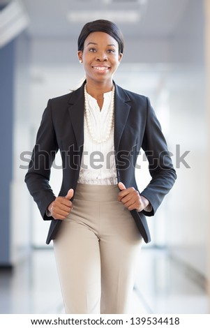 Young African-american professional woman walking down a hallway towards camera, smiling, wearing blazer, pearls - stock photo