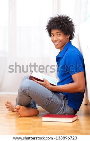 Young african american student seated on the floor reading books - African people