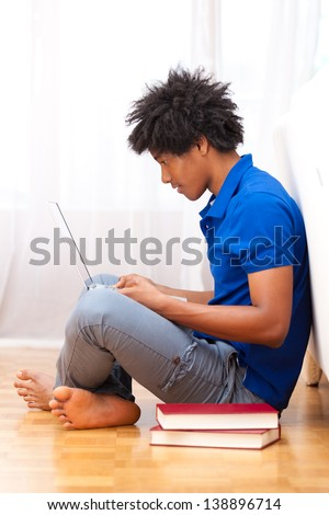 Young african american student seated on the floor using a laptop - African people - stock photo