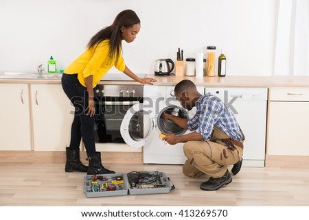 Young African American Technician Repairing Washing Machine In Kitchen