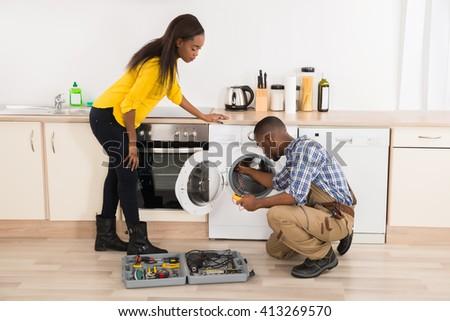 Young African American Technician Repairing Washing Machine In Kitchen