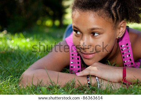 Young african american teenage girl  lying on the grass - stock photo