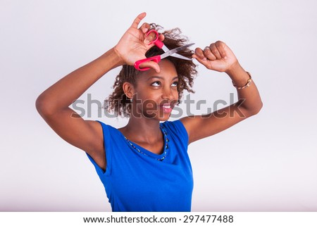 Young African American woman cutting her frizzy afro hair with scissors - Black people - stock photo