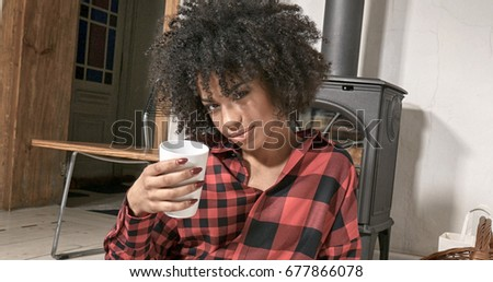 Young african american woman drinking coffee at home, sitting on the floor. Girl with afro hairstyle.