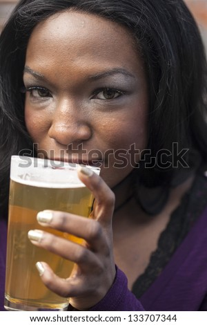 Young African American woman drinks a pale ale from a pint glass. - stock photo