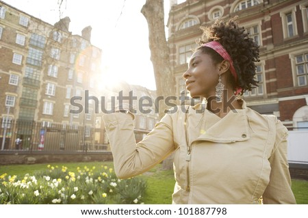 Young african american woman holding the sun in her hand at sunset in the city of London. - stock photo
