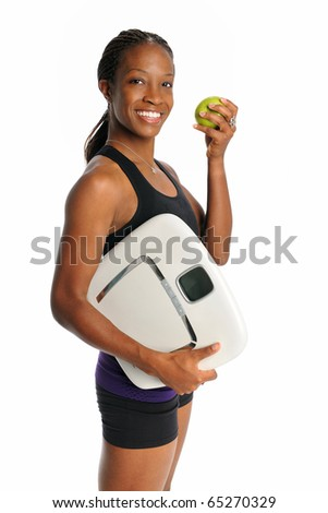 Young African American woman holding weight scale and apple isolated over white background