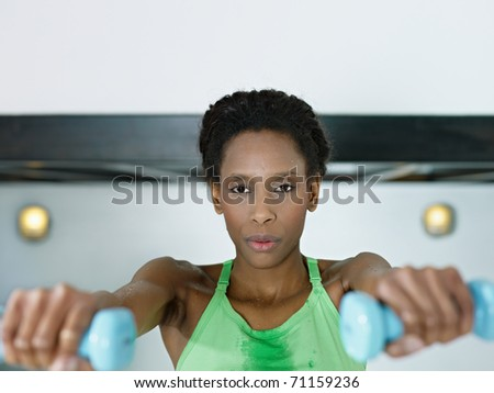 young african american woman in green sportswear doing weight lifting in fitness club. Horizontal shape, front view, copy space