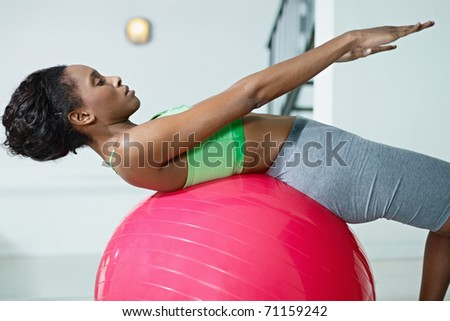 young african american woman in green sportswear exercising abdominals on fit ball in gym. Horizontal shape, side view, three quarter length