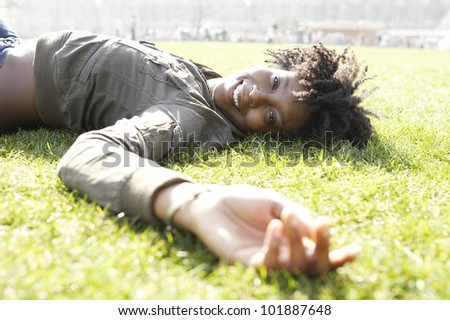 Young african american woman laying down on green grass in the city, on a sunny day.