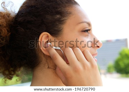 Young african american woman listening to music with earphones in ears - stock photo