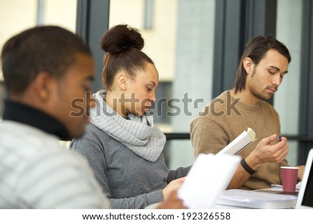 Young african american woman reading notes with classmates studying around in university library. Students preparing hard for final exams. - stock photo