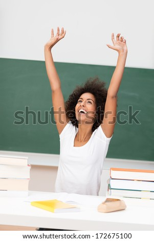 Young African American woman rejoicing stretching her hands into the air with a smile of joy and jubilation - stock photo