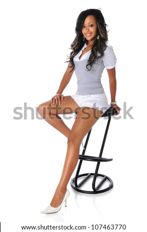 Young African American woman sitting on stool isolated over white background - stock photo