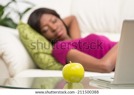 young African American woman sleeping on sofa. pretty black girl relaxing on sofa in her living room - stock photo