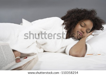 Young African American woman sleeping while holding a book - stock photo
