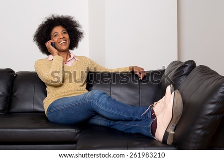young african american woman talking on the phone at home - stock photo