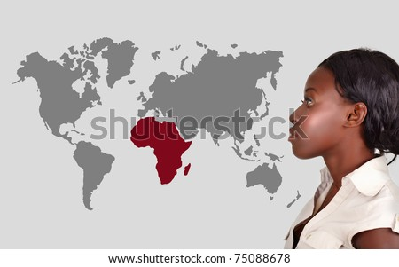 young African American woman thinking and looking at the world map with Africa in red. - stock photo