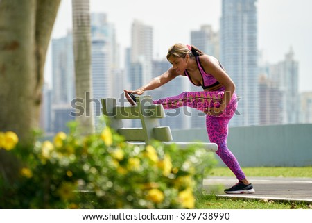 Young african american woman warming up before starting her daily sport routine. The girl trains at early morning along the Cinta Costera in Panama. Long shot - stock photo