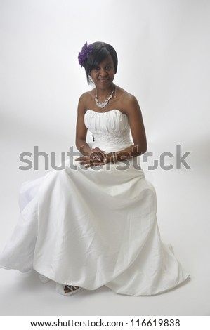 Young african american woman wearing wedding dress on white background - stock photo