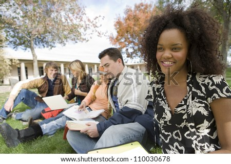 Young African American woman with friends studying at college campus - stock photo