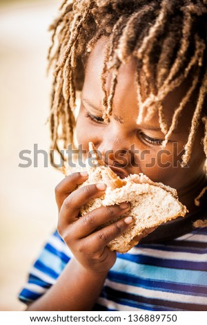 young african boy with rasta dreadlocks enjoying a cold meat sandwich - stock photo