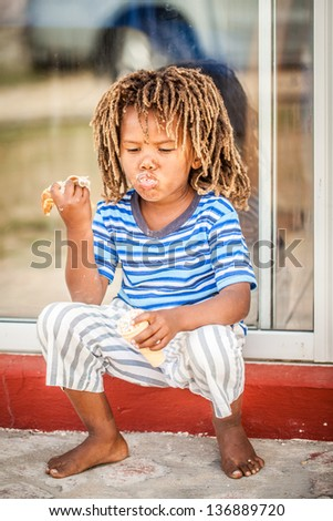 young african boy with rasta dreadlocks hair playing with his food in his mouth sitting on a red step - stock photo