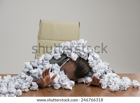 Young african business woman covered in crumpled papers against gray background - stock photo