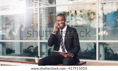 Young African businessman smiling on city bench with phone, tablet - stock photo