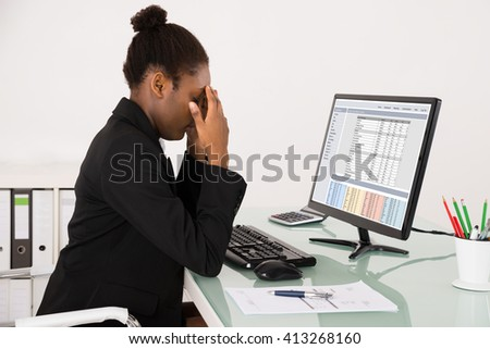Young African Businesswoman Suffering From Headache While Working At Workplace - stock photo