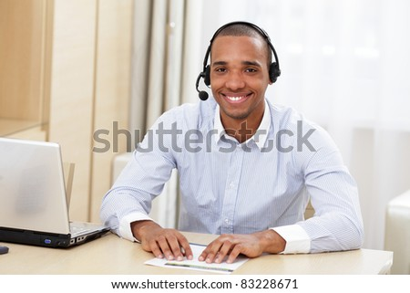 young african call center consultant with headset in office