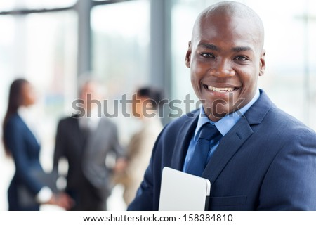 young african corporate worker in modern office with colleagues on background