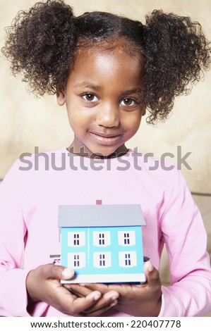 Young African girl holding tiny house - stock photo