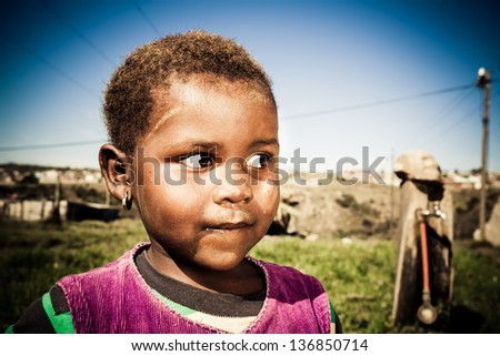 young african girl looking curiously at something that caught her eye in the outdoors
