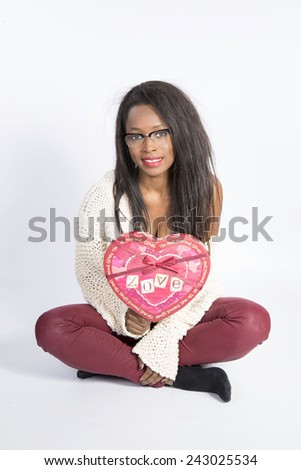 Young African girl sitting with heart of San Valentin - stock photo