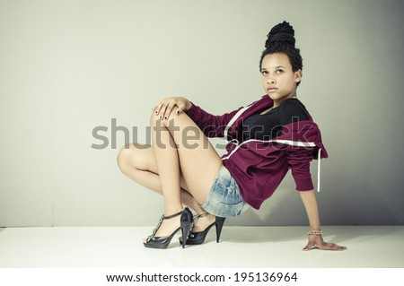 Young african girl with black dreadlocks wearing trendy hip-hop fashion and posing in front of a grey wall. - stock photo